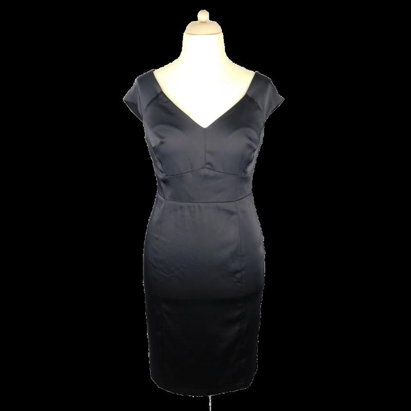Fekete, alakot követő ruha, enyhén rugalmas anyagból, elöl-hátul V-kivágással. Hátul cipzárral záródik